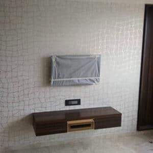 Geometric wallpaper behind tv unit